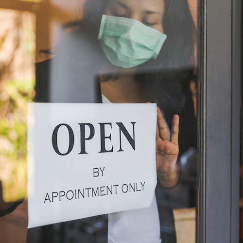 woman putting up sign open by appointment